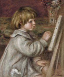young boy painitng at an easle