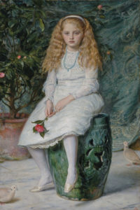 young girl seated with a flower in her hand