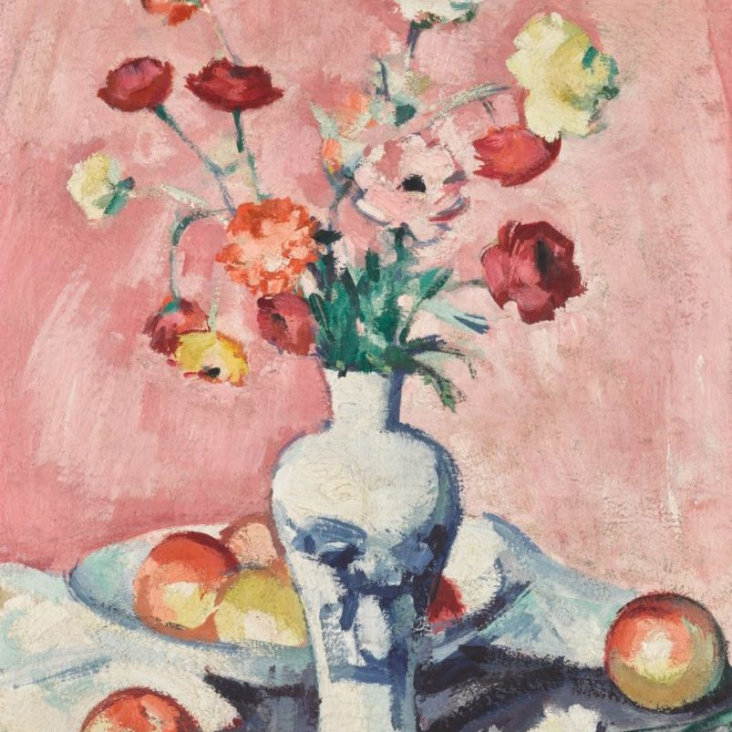 flowers in a vase with fruit on a table