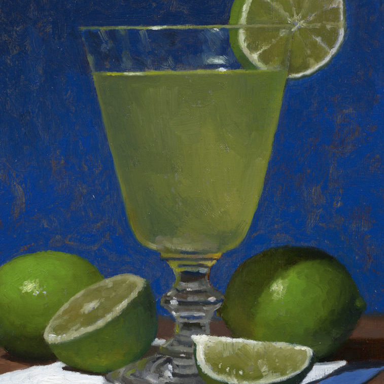a glass with a cocktail and limes