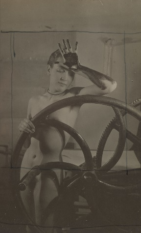 A nude woman behind a wheel